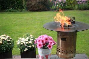 Holz nachlegen in die Feuertonne mit Feuerplatte