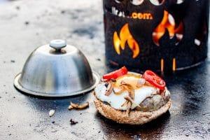 Hamburger auf der Feuerplatte mit Burgerglocke