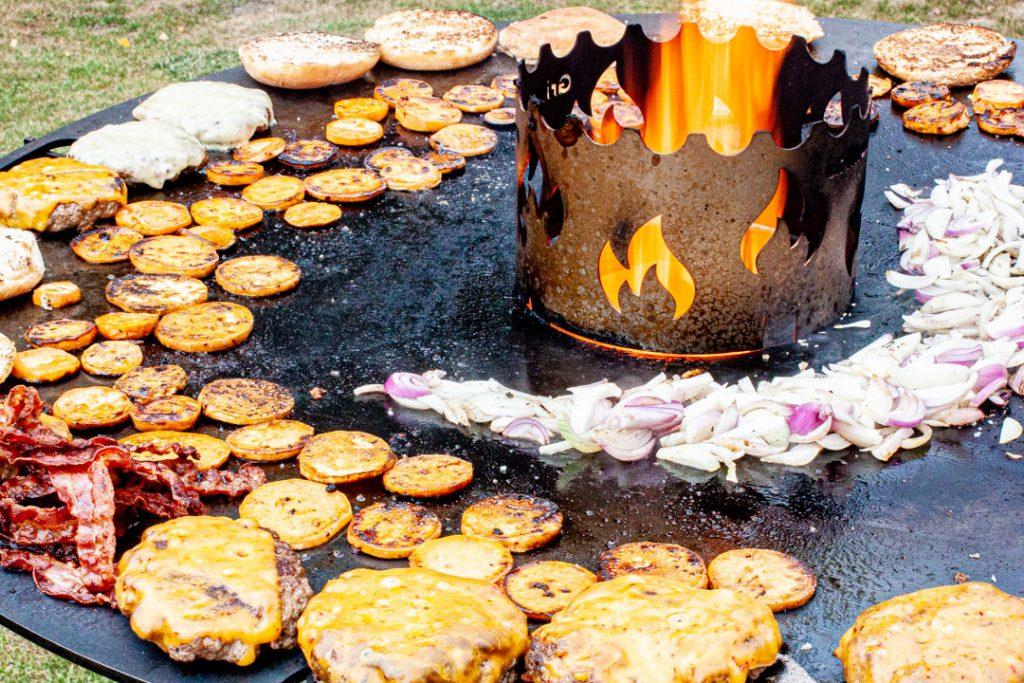 Süßkartoffelchips, Zwiebeln, Bacon und Hamburger auf der Feuerplatte
