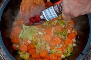 Tomatenmark zum Suppengemüse im Dutch Oven geben