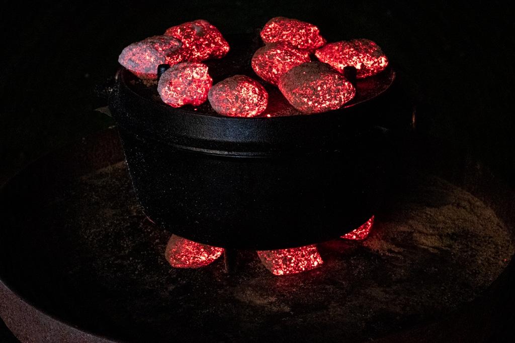 Dutch Oven mit glühenden Holzkohlebriketts