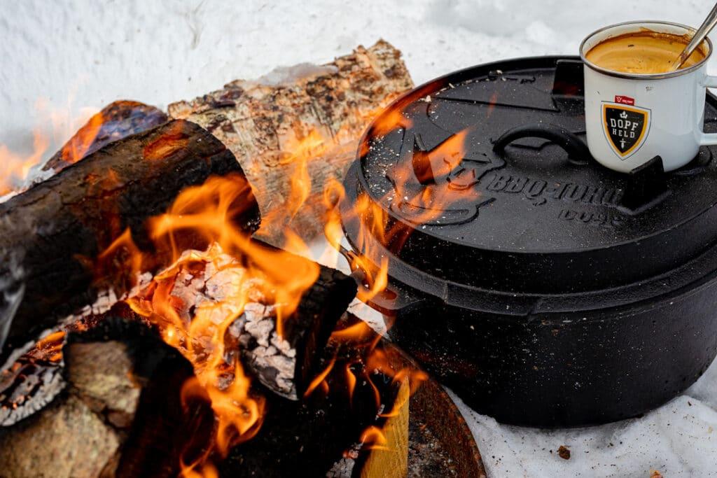 Dutch Oven am Feuer mit Kaffeetasse