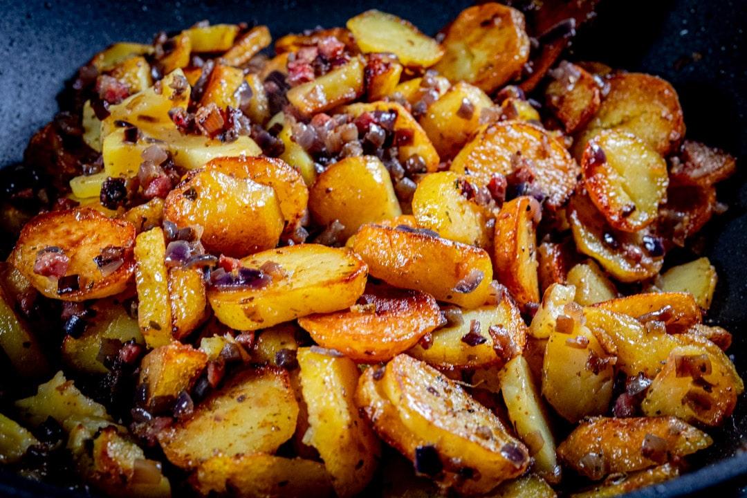 Bratkartoffel in der Bratpfanne mit Speck und Zwiebeln